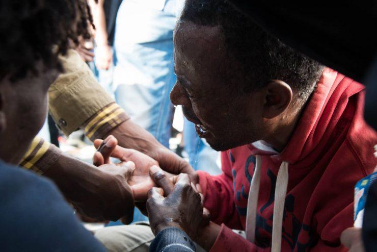 Été 2015, un réfugié a été frappé par la police. Des proches lui mettent de l'eau sur le visage pour l'apaiser. Ce jour là, va commencer l'occupation de la rue Pajol, occupation qui durera une partie de l'été 2015.